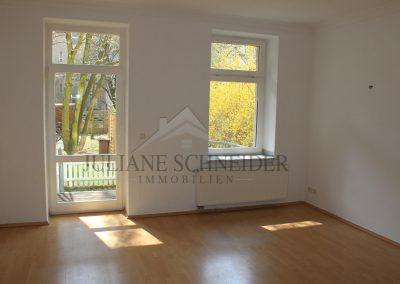 Wohnzimmer mit offener Küche und Zugang zum Balkon
